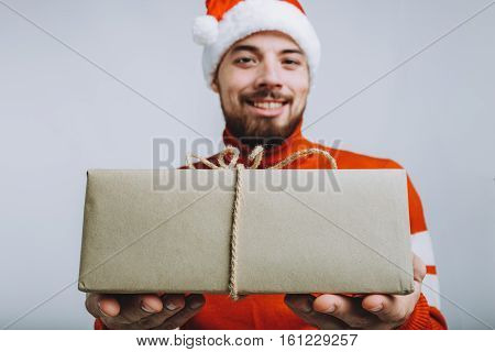 Handsome man offering a christmas gift. Smiling guy is proposing big present for you at camera. Isolated on white background