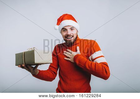 Handsome man in Santa's hat holding a christmas gift. Happy guy put his hand on chest asking whether this present is for him. He would be glad to get it. Isolated on white background