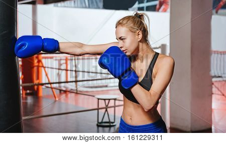 Punch. Attractive athletic determined girl with a ponytail mastering her punch on punch bag in gym while wearing special sportswear