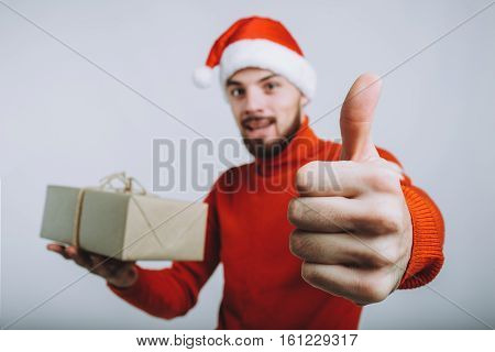 Handsome man in warm red sweater holding a christmas gift. Smiling guy in Santa's hat is pointing at camera with his lifted up thumb that everythng is ok. Isolated on white background