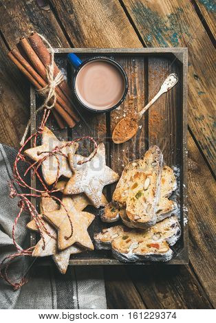 Cocoa in mug with Christmas gingerbread star shaped cookies and pieces of Stollen cake in wooden tray over rustic wooden background, top view, vertical composition