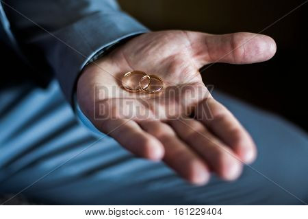 gold wedding ring in a man's hand the groom holding rings wedding bands on a dark background