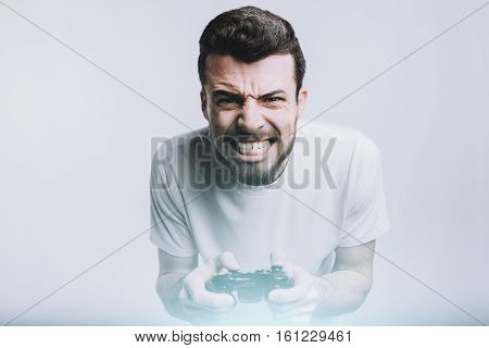Young stylish man with beard holding joystick and trying to win this hard game battle. He is really concentrated and serious. Isolated on white background