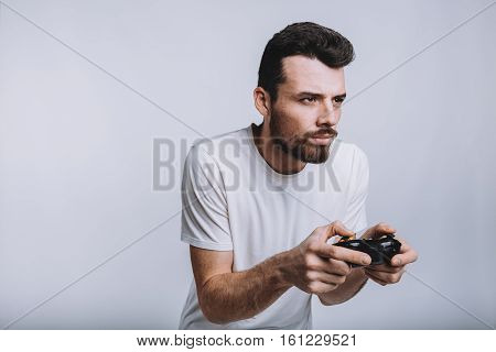 Young attractive guy with beard holding joystick. Funny man is really concenrated on serious game. He is going to win that tough battle. Isolated on white background