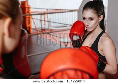 Intense sparring. Beautiful strong young woman with hazel eyes having a sparring with her friend in a gym