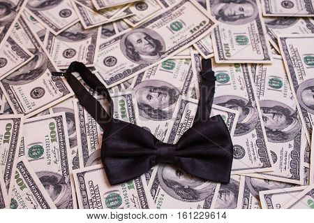 black bowtie lying on the background of hundred-dollar bills background of the money hundred dollar bills front side. background of dollars old hundred-dollar bill face