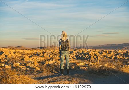 Young woman traveller wearing hoodie, backpack and jeans standing and watching sunrise in mountains over Goreme, Cappadocia, Central Turkey