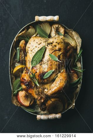 Oven roasted whole chicken with onion, apples and sage in metal serving tray over dark stone background, top view, selective focus. Celebration food concept