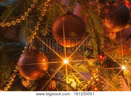 Christmas ornaments and garland on the Christmas tree with stars from the lamps