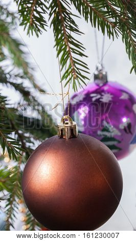 Christmas ball on a branch on a background glass with frost and colorful blurred lights