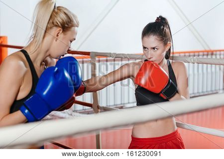 Not so aggressive. Attractive athletic focused women having an intensive workout in a gym while fighting a bout wearing special equipment