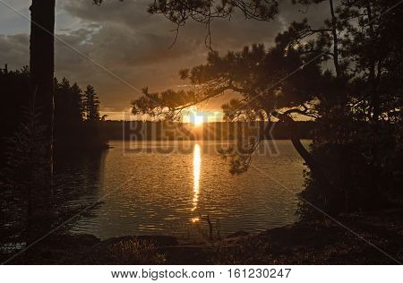 Sun Peeking Through at Sunset on Agnes Lake in Quetico Provincial Park in Ontario