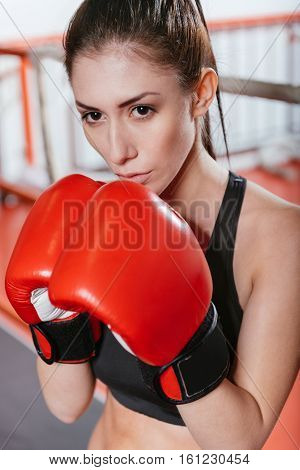 Powerful beauty. Stunning strong female athlete wearing bright red boxing gloves and posing while standing in a classic guard