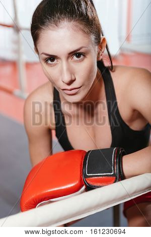 Close up beauty. Attractive hazel eyed athletic woman sitting in the ring posing for a photo while wearing boxing gloves