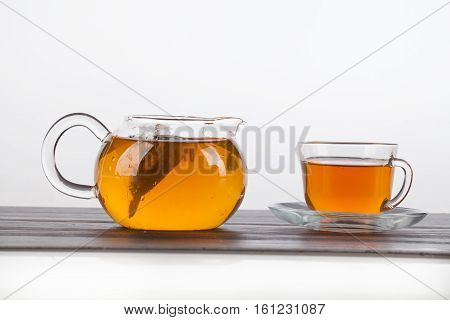Glass teapot and cup of tea on an isolated studio background