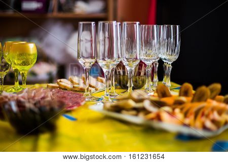 empty glasses stand on a festive table with food preparation for the wedding feast