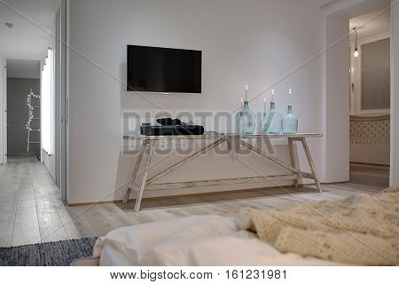 Interior in a modern style with white walls and a parquet with a carpet on the floor. There is a wooden table with candles in bottles, soundbar and a shawl, TV, bed with a plaid, doors, glowing lamps.
