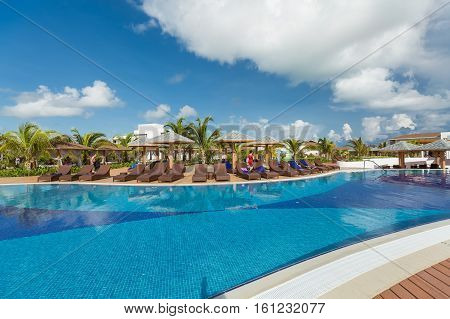 Cayo Coco island, Pullman hotel, Cuba, June 28, 2016, stunning beautiful inviting view of resort outdoor swimming pool and hotel grounds with people relaxing in background on sunny gorgeous day