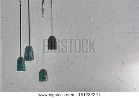 Four hanging malachite lamps on the white brick wall background. Closeup. Horizontal.