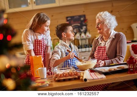 smiling children and grandmother preparing Xmas cookies-Family time