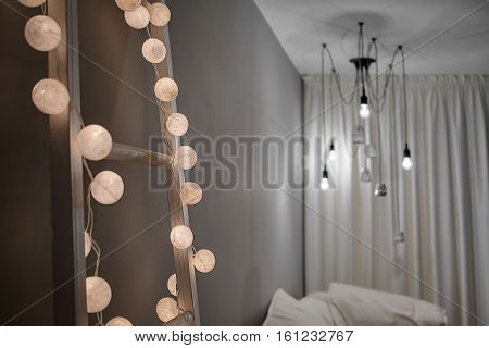 Wooden ladder with the glowing sphere lamps in a form of the garland on the gray wall background. There is a sofa, curtains and glowing hanging lamps with decorations. Closeup. Horizontal.
