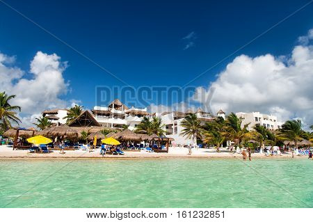 Mexico, Costa Maya - February 1 2016: tropical beach at transparent sea or ocean water with sunbeds on white sand with green palms tourist resort on sunny summer day on blue sky