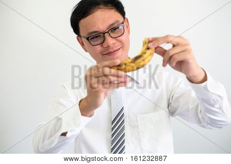 portrait of young ceo bussinessman thinking with banana.