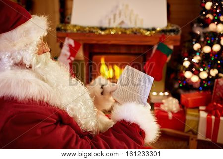 Smiling Santa Claus sitting and reading children wishes for x-mas