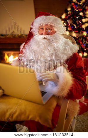Santa Claus reading email on laptop requesting wish present list children