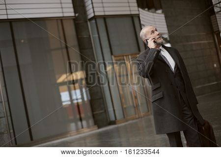 Businesman waitinf for the taxi and talking on the phone