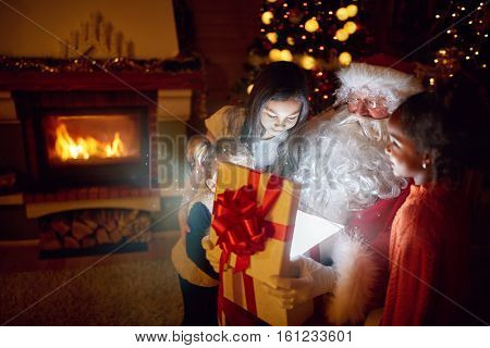 Santa Claus with  magic present surrounded with curiosity children