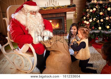 Children eagerly waiting gift from Santa Claus sack