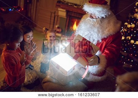Traditional Santa Claus with children and magical present, open gift box with magical effect