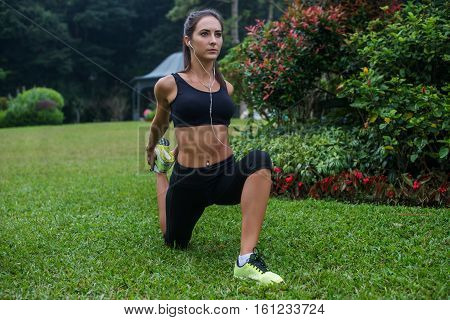 Fit girl doing kneeling quads stretch exercise in park. Young athletic woman working out and listening to music in her headphones outdoors