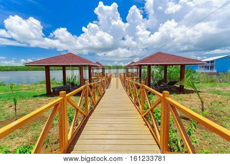 nice beautiful amazing view of cozy inviting walk way trough a wooden bridge, leading to comfortable relaxing gazebos near ocean bay in tropical gaeden