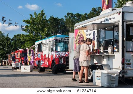 KENNESAW, GA - AUGUST 2016:  A row of colorful food trucks serves customers at the Great Southern Food Truck Rally in Kennesaw GA on August 27 2016 .