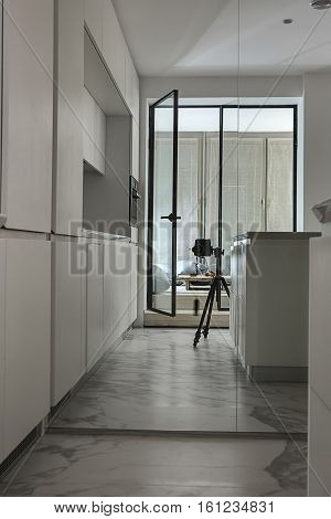 Reflection in the mirror of the modern kitchen zone and a glass door  entrance to the glowing room with tall windows with curtains. There is a black DSLR on the tripod. Vertical.