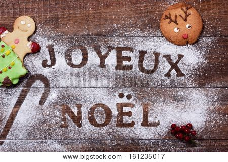 high-angle shot of a wooden table sprinkled with icing sugar or flour where you can read the text joyeux noel, merry christmas in french, and some christmas cookies