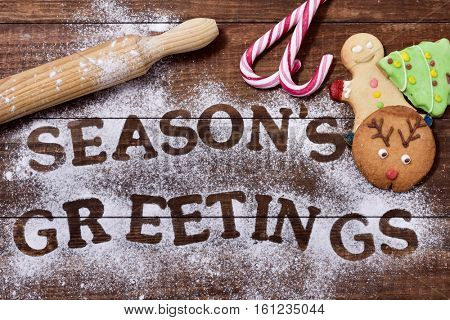 high-angle shot of a wooden table sprinkled with icing sugar or flour where you can read the text seasons greetings, a rolling pin, some candy canes and some christmas cookies