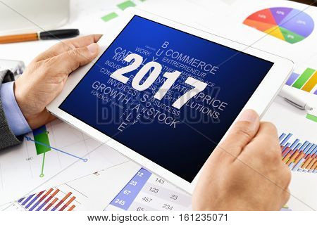 a young caucasian businessman sitting at his office desk full of charts watching his tablet computer with a tag cloud of goals for 2017 in its screen