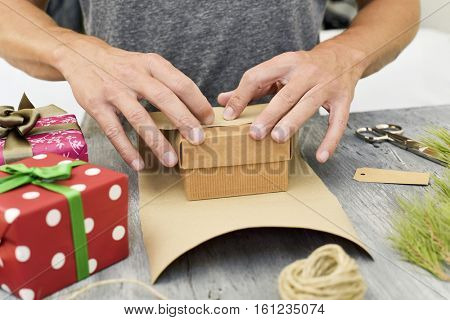 closeup of a young caucasian man wrapping a gift on a rustic wooden surface with some gifts, natural branches, a roll of jute string and a pair of scissors