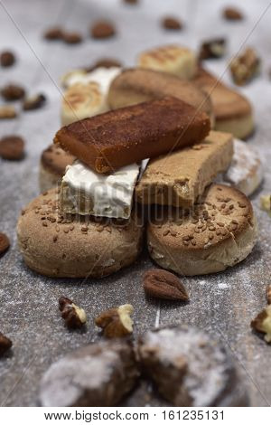 closeup of a pile of different turron, mantecados and polvorones, typical christmas sweets in Spain, on a rustic wooden table