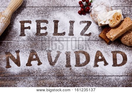 high-angle shot of a wooden table sprinkled with icing sugar or flour where you can read the text feliz navidad, merry christmas in spanish, a rolling pin and some mantecados and some pieces of turron