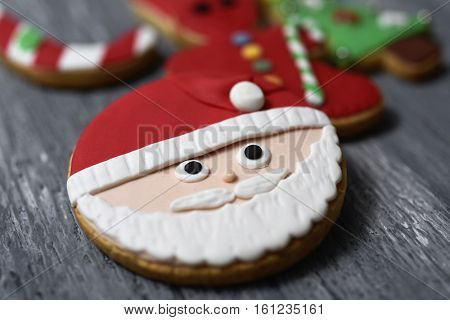 closeup of an assortment of christmas cookies with different shapes and colors on a rustic wooden surface