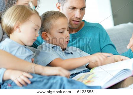 Family sitting on sofa reading book with kids