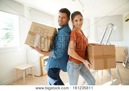 Couple holding cardboards in brand new house