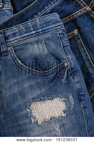 Pile of blue denim jeans isolated
