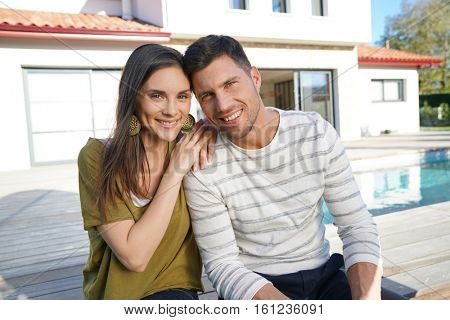 Cheerful young couple sitting in front of new home