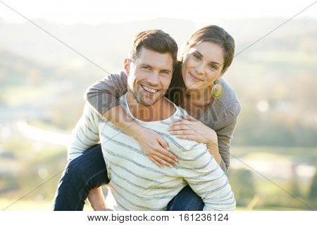 Portrait of cheerful man giving piggyback ride to girlfriend