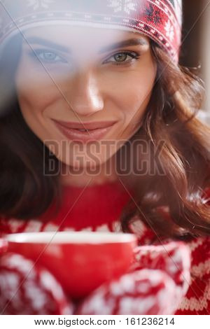 Young happy woman in warm sweater drinking a cup of hot tea
